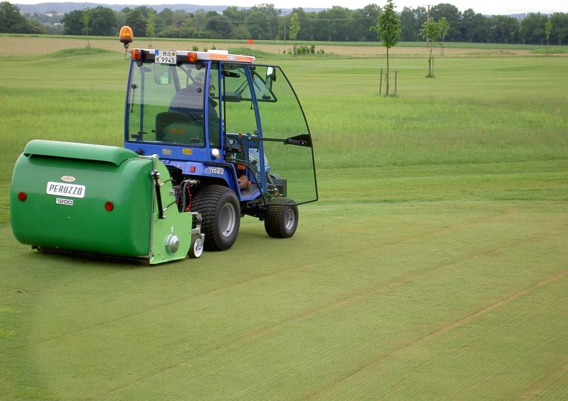 Mini flail scarifier collector on golf green